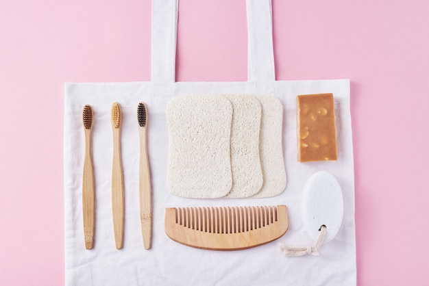 Soins du corps produits naturels écologiques en bois sur une vue de dessus rose et plate. brosses à dents en bambou, peigne en bois, savon, éponge et produits de lavage naturels. zero gaspillage Photo Premium
