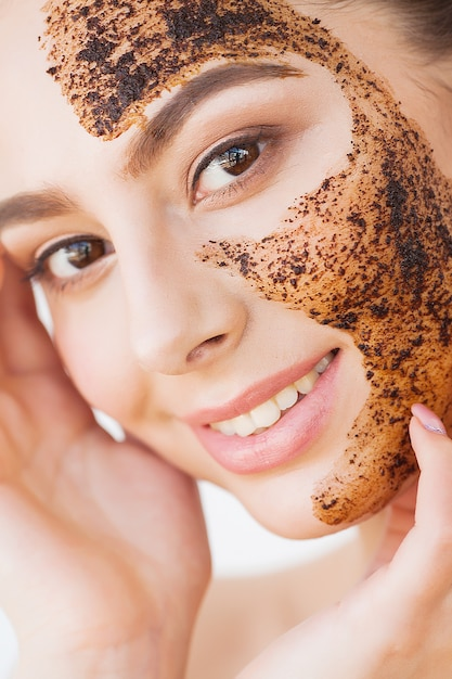Soins du visage. jeune fille charmante fait un masque de charbon noir sur son visage Photo Premium