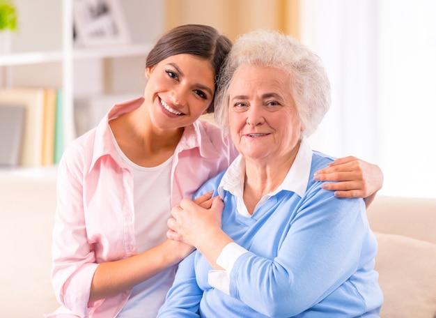 Soins d'une femme âgée à la maison assise sur le canapé Photo Premium