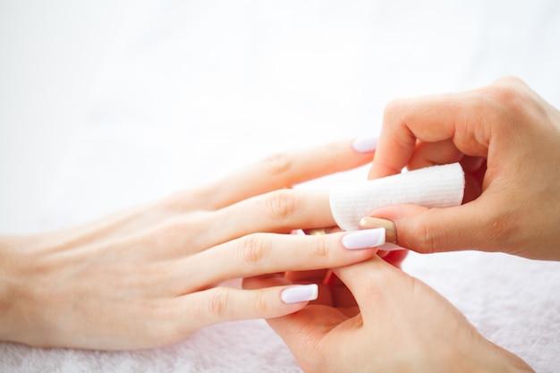 Soins des mains et des ongles. mains de belles femmes avec une manucure parfaite. maître de manucure tenant des tampons de coton dans les mains. journée de la beauté. spa manucure Photo Premium
