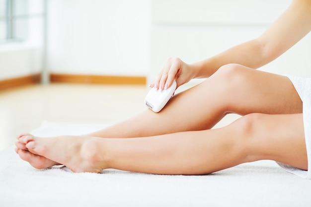 Soins de la peau et de la santé. épilation. femme épilateur jambe, épilateur électrique blanc Photo Premium