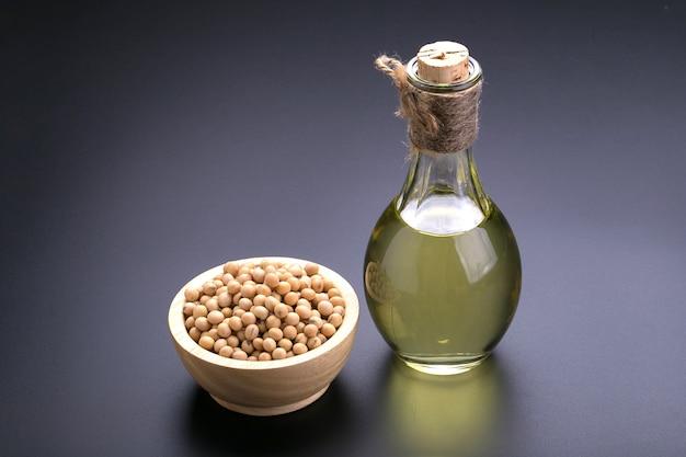 Soja dans un bol en bois et l'huile de soja sur un fond noir Photo Premium