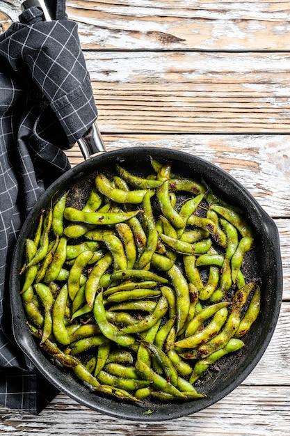 Soja Edamame Vert Cuit Dans Une Casserole, Nourriture Japonaise. Fond Blanc. Vue De Dessus Photo Premium