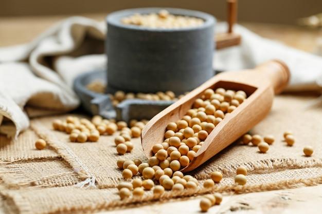Le soja en pelle à bois et un petit moulin à pierre Photo gratuit