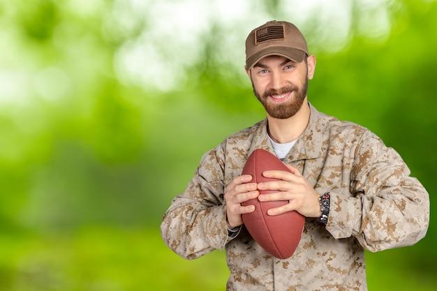 Soldat américain tenant un ballon de football Photo Premium