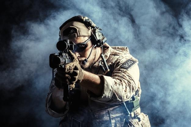 Soldat des forces spéciales avec fusil dans l'obscurité Photo Premium