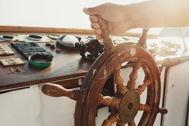 Le soleil brille sur la roue en bois tenue par l'homme Photo gratuit