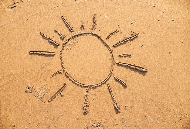 Soleil dessiné dans le sable Photo gratuit