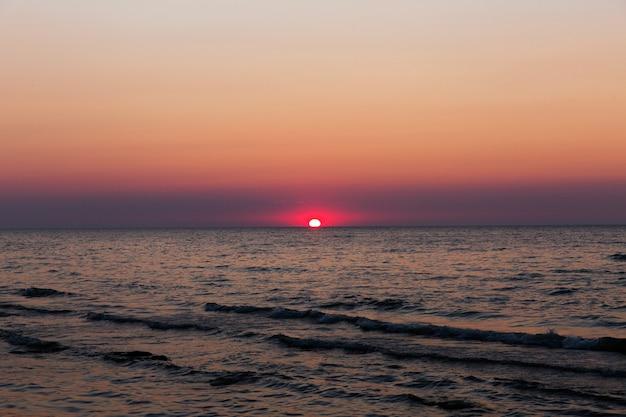 Soleil rouge sur un coucher de soleil coucher de soleil sur la mer beau paysage de soirée. vagues dans une mer au coucher du soleil Photo Premium