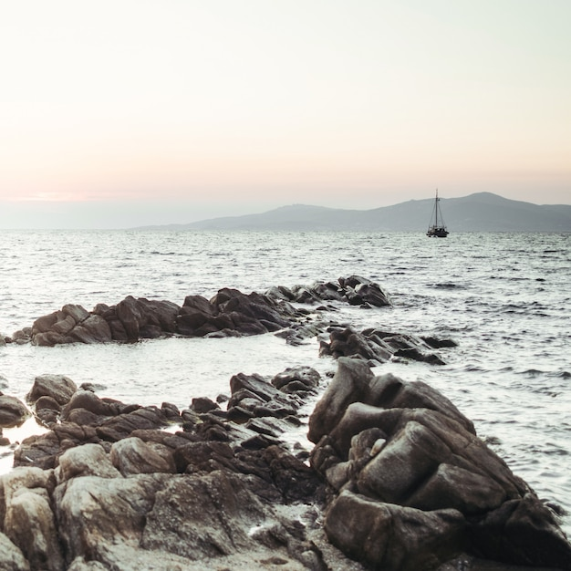 Le soleil se couche sur la mer et les rochers noirs devant elle Photo gratuit
