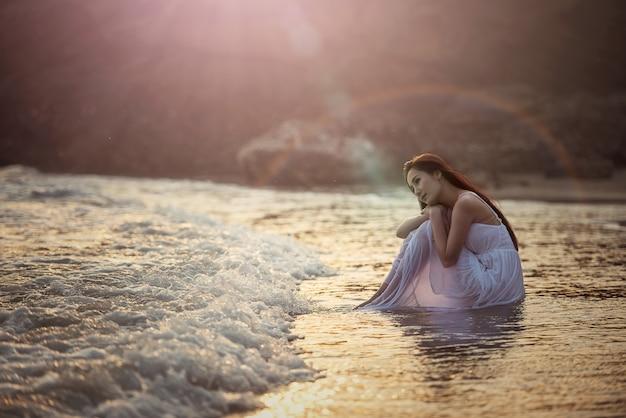Solitaire jeune femme sur la plage Photo Premium