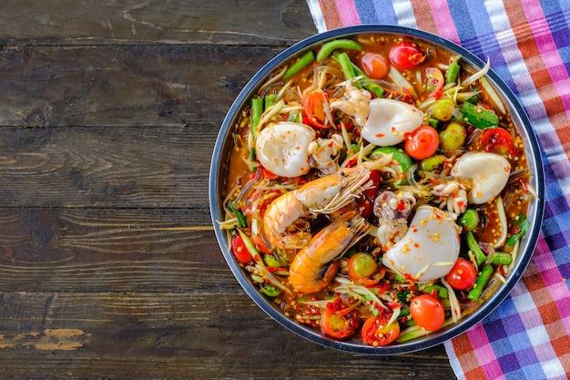 Som Tam Seafood (salade De Papaye épicée) Au Crabe Salé, Sur Une Table En Bois Photo Premium
