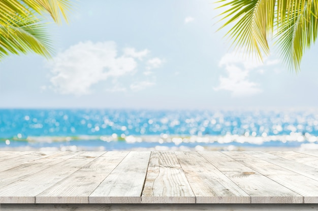 Sommet De La Table En Bois Avec Paysage Marin Et Feuilles De Palmier, Flou De Lumière Bokeh De Mer Calme Et Ciel à La Plage Tropicale Photo Premium