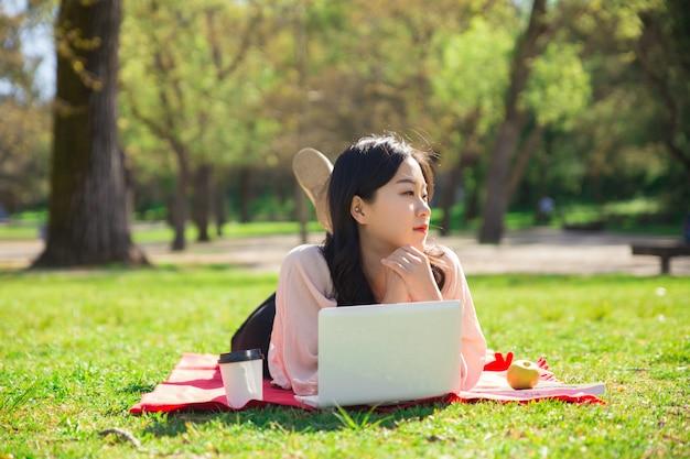 Songeuse femme asiatique travaillant sur un ordinateur portable sur la pelouse Photo gratuit
