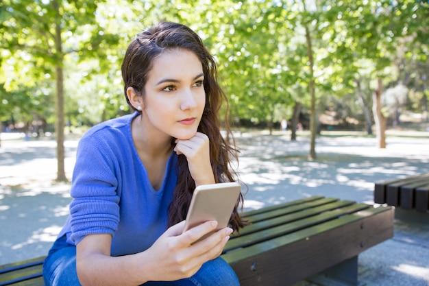 Songeuse Jeune Femme à L'aide De Smartphone Dans Le Parc Photo gratuit