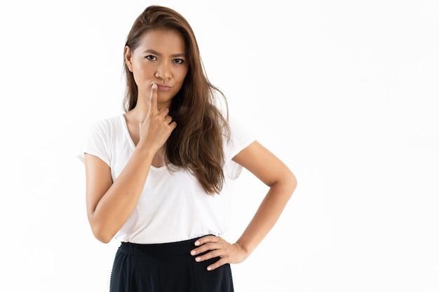 Songeuse jeune femme souriante touchant les lèvres Photo gratuit