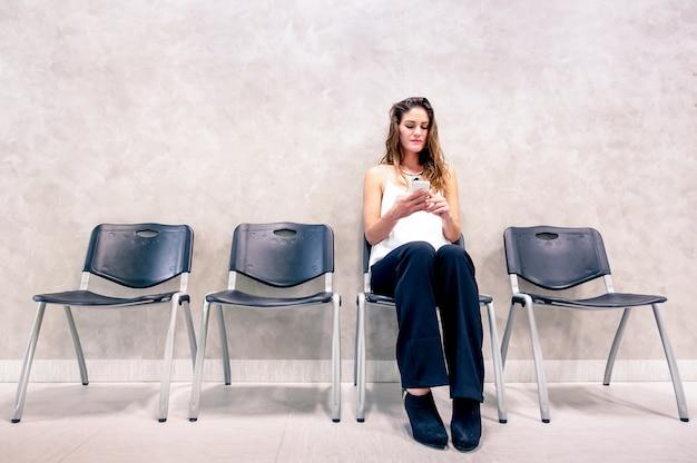 Songeuse jeune femme avec un téléphone intelligent mobile assis dans la salle d'attente Photo Premium