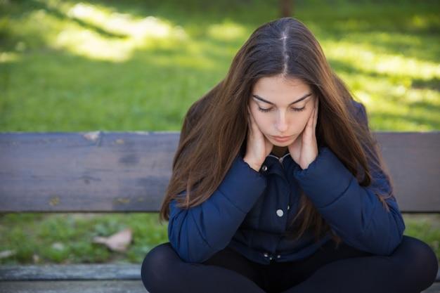 Songeuse jolie femme assise sur un banc dans le parc Photo gratuit
