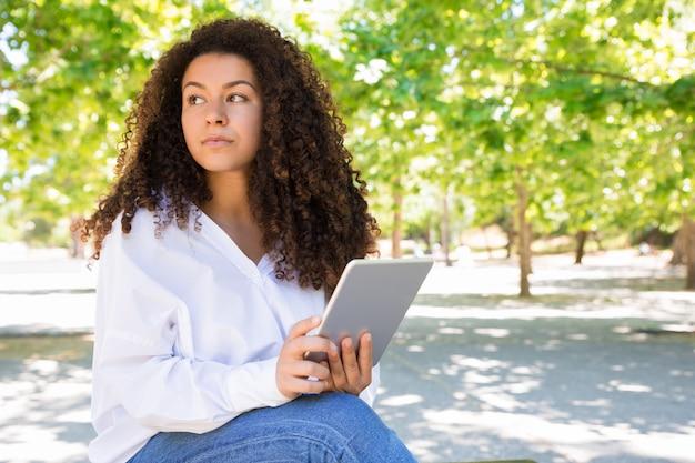 Songeuse jolie jeune femme à l'aide de tablette sur un banc dans le parc Photo gratuit