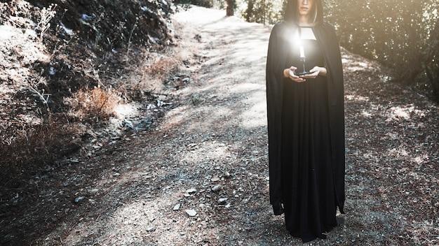 Sorcière au cap tenant un chandelier sur le chemin forestier Photo gratuit