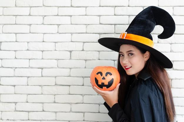 Sorcière d'halloween avec une citrouille magique, belle jeune femme en costume et chapeau de sorcière Photo Premium
