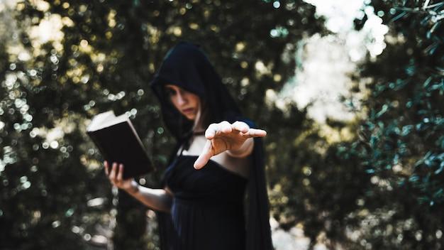 Sorcière avec un livre utilisant la magie dans le fourré Photo gratuit