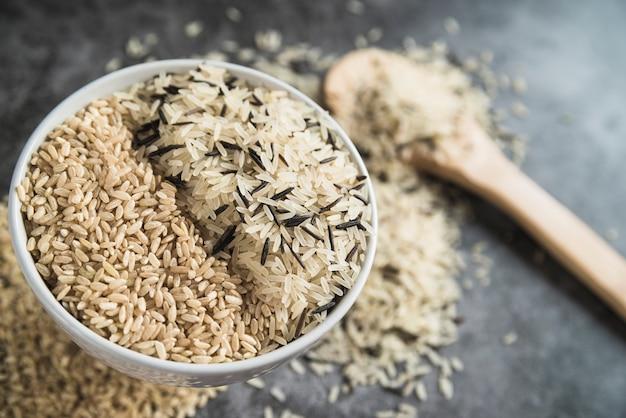 Sortes de riz dans un bol près de la cuillère en bois Photo gratuit