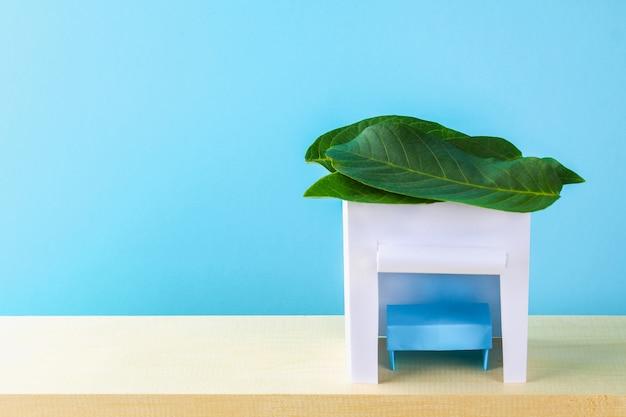 Souccot heureux. une hutte en papier recouvert de feuilles sur fond bleu. copiez l'espace. Photo Premium