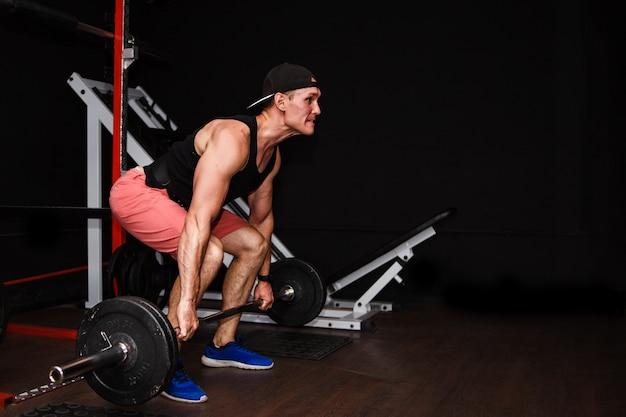 Soulevé de terre. homme sportif soulevant barbell row au gymnase Photo Premium