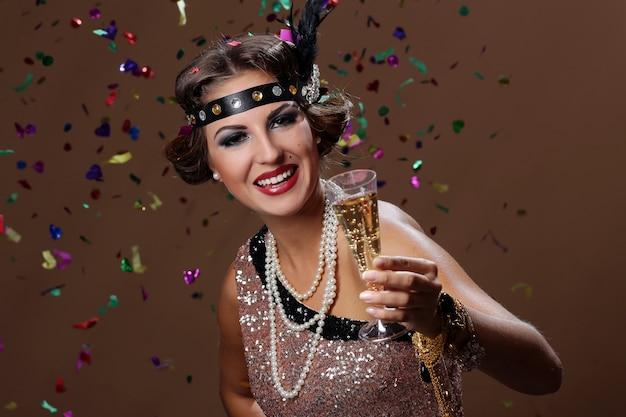Soulever son verre avec du vin et des confettis Photo gratuit