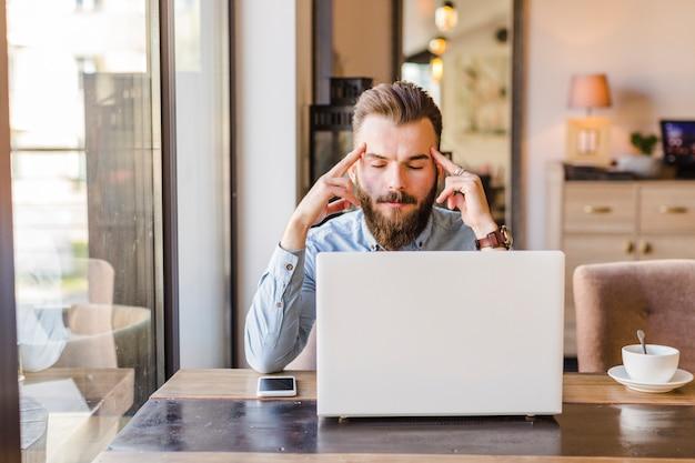 A souligné le jeune homme assis dans un café avec ordinateur portable sur le bureau Photo gratuit