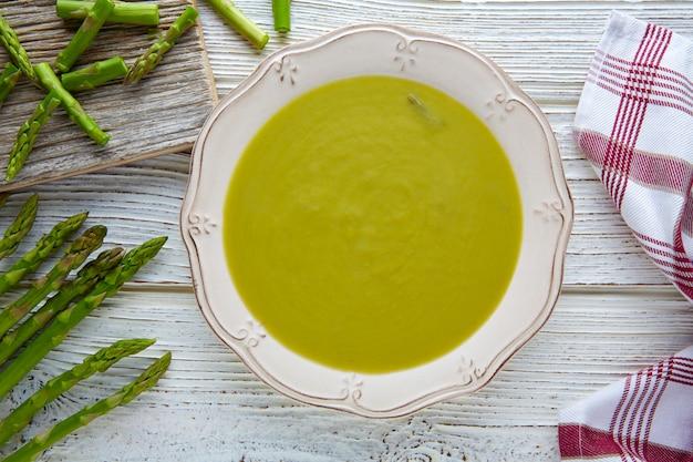 Soupe d'asperges vert crème sur une table en bois blanc Photo Premium