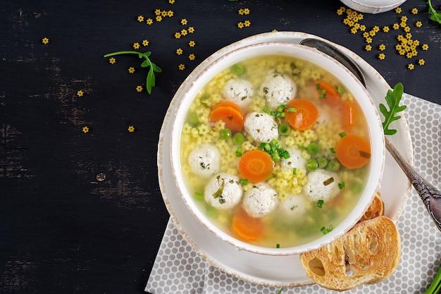 Soupe Aux Boulettes De Viande Italienne Et Pâtes Stelline Dans Un Bol Sur Le Tableau Noir. Photo gratuit