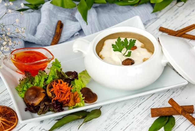 Soupe aux champignons en céramique servie avec salade et sauce Photo gratuit