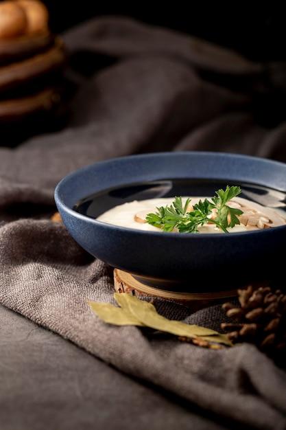 Soupe aux champignons dans un bocal bleu sur un drap gris Photo gratuit