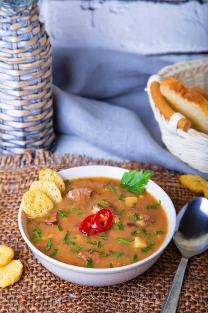 Soupe Aux Petits Pois Avec Viande, Saucisse Fumée Et Croûtons. Photo Premium