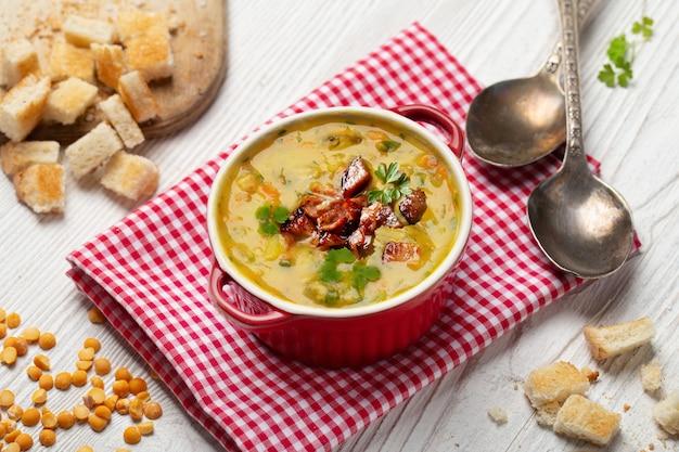 Soupe Aux Pois Avec Des Morceaux De Bacon Et De Persil Dans Un Bol Sur Fond Blanc Photo Premium