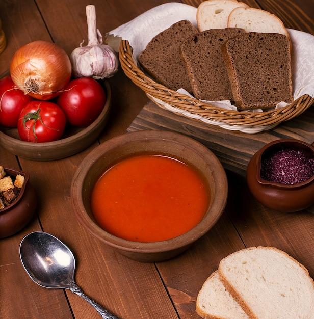 Soupe Aux Tomates Dans Un Bol En Terre Cuite Servie Avec Des Légumes Et Du Pain Brun En Tranches. Photo gratuit