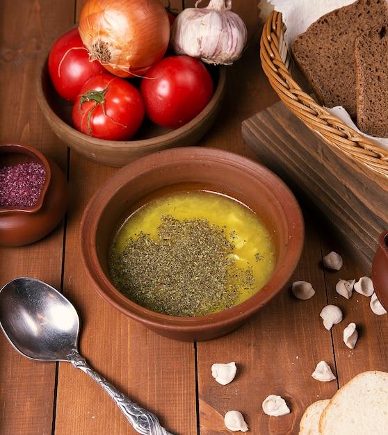 Soupe de bouillon de poulet aux herbes et légumes. servi dans un bol en poterie avec du sumakh. Photo gratuit