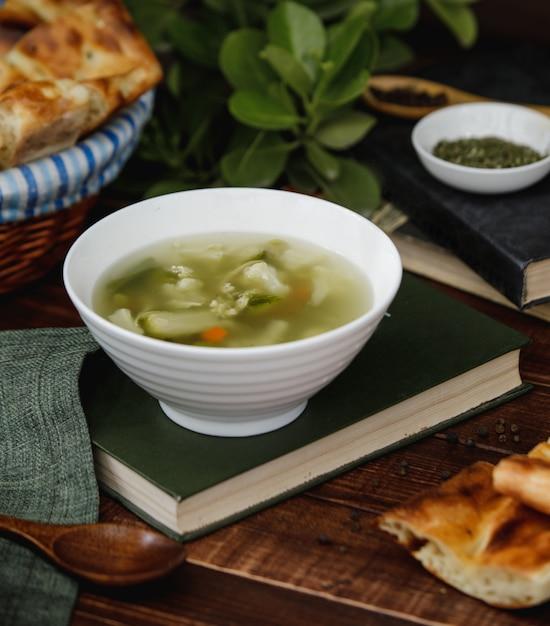 Soupe de bouillon de poulet aux légumes dans un bol blanc servi avec du pain Photo gratuit