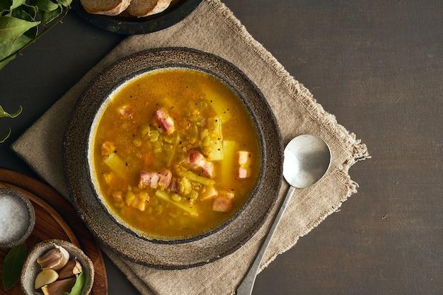 Soupe chaude d'hiver aux pois verts hachés, porc, bacon, fumé sur une table en bois brun foncé Photo Premium