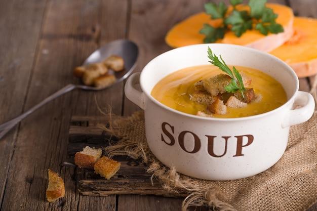 Soupe à La Citrouille. Soupe Végétarienne Aux Graines De Citrouille Dans Un Bol Sur Une Table En Bois, Vue Du Dessus Photo Premium