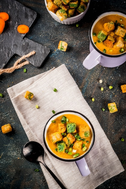 Soupe à la crème de carottes en purée maison, avec des craquelins de pain, des herbes fraîches et de la crème Photo Premium