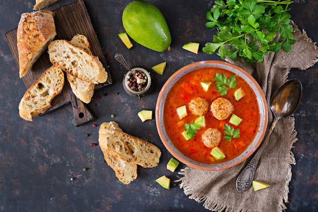Soupe épicée Aux Tomates Avec Boulettes De Viande Et Légumes. Servi Avec Avocat Et Persil. Dîner Sain, Plat. Photo Premium