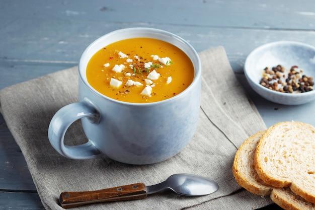 Soupe épicée à La Citrouille Et Aux Patates Douces Dans Une Grande Tasse En Céramique Garnie De Fromage Feta. Photo Premium