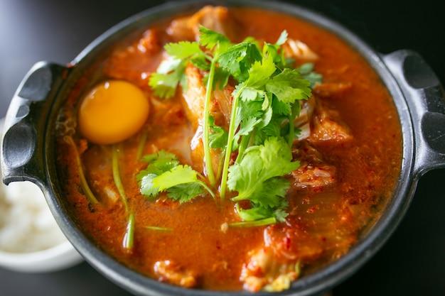Soupe de kimchi avec des œufs de poulet crus et du tofu blanc, nourriture coréenne populaire Photo Premium