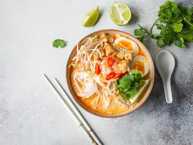 Soupe Laksa De Nouilles Malaisiennes Au Poulet, Crevettes Et Tofu Dans Un Bol Sur Une Surface Grise Photo Premium