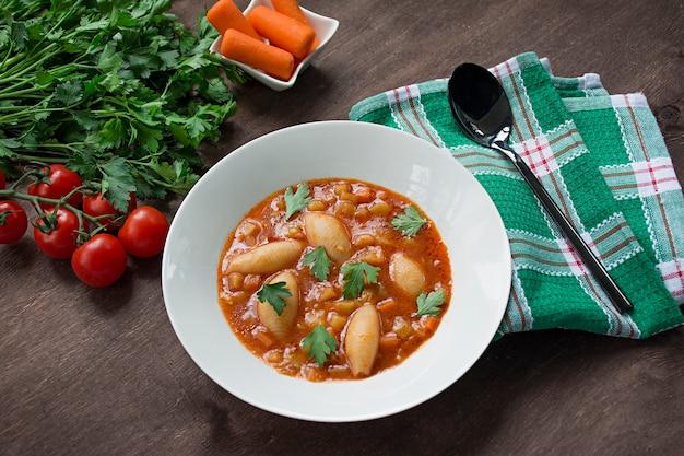 Soupe minestrone avec des pâtes et des herbes. cuisine italienne. fond de bois blanc Photo Premium
