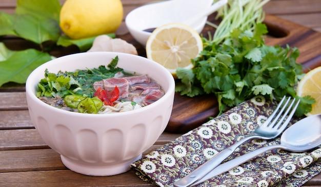 Soupe de nouilles vietnamienne avec bouillon, nouilles au riz en forme de linguine, coriandre et bœuf Photo Premium