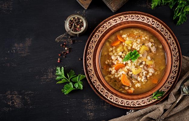 Soupe d'orge aux carottes, tomates, céleri et viande sur un fond sombre Photo Premium